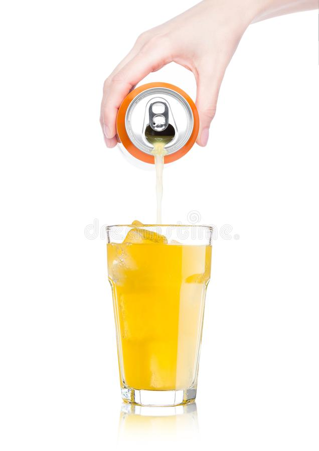 Female hand pouring orange soda from can to glass. Female hand pouring orange soda drink from aluminium can to glass with ice cubes on white background stock photo