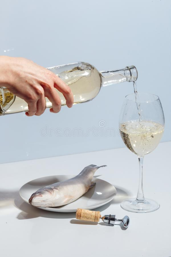 Female hand pours white wine into a glass. Minimalistic creative concept royalty free stock photos