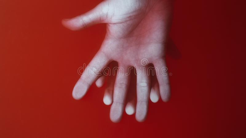 Female hand pressed to the glass by the male palm in red water, the concept of mysterious love, cover for art in horror genre. Female hand pressed to the glass royalty free stock photos