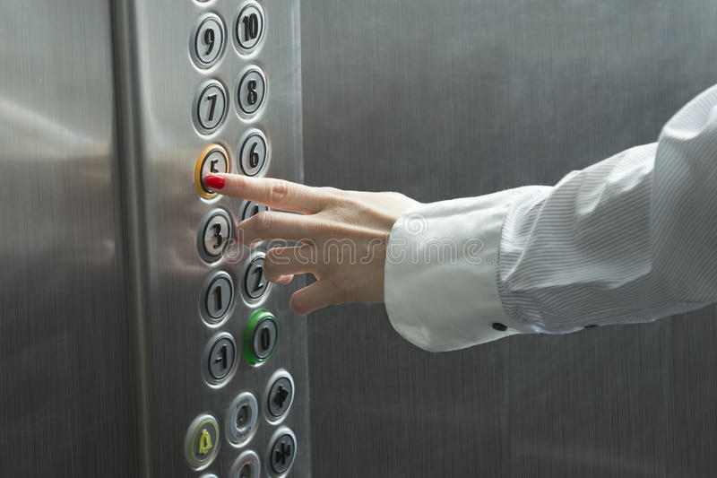 Female hand pressing the button in the elevator stock photo