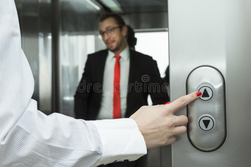 Female hand pressing elevator up button. Businessman inside of the elevator. stock photos