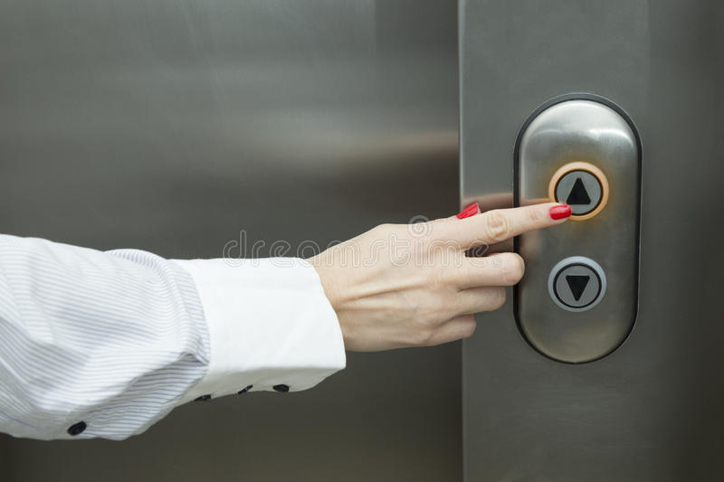 Female hand pressing elevator up button royalty free stock photography