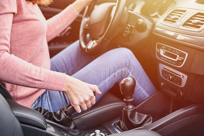 Female hand pulling handbrake in the car. Woman driving the car stock photos