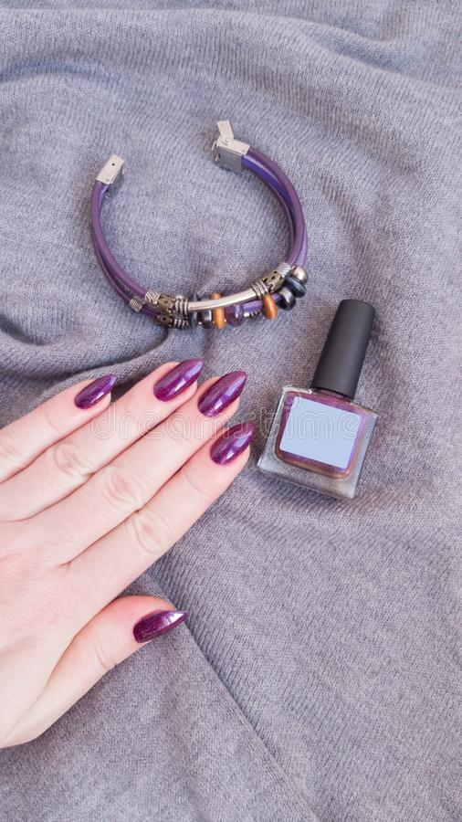 Female hand with purple long nails and nail polish bottle. Female hand with purple long nails manicure and nail polish bottle royalty free stock photography