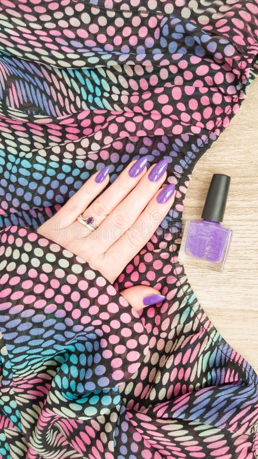 Female hand with purple violet long nails. And nail polish bottle royalty free stock images
