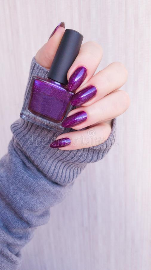 Female hand with purple violet long nails. And nail polish bottle stock image