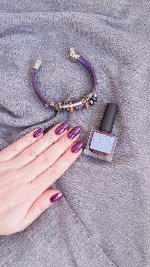 Female hand with purple violet long nails. And nail polish bottle stock photos
