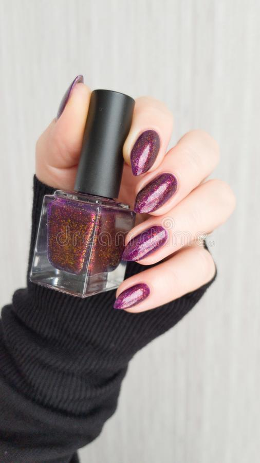 Female hand with purple violet long nails. And nail polish bottle royalty free stock photo