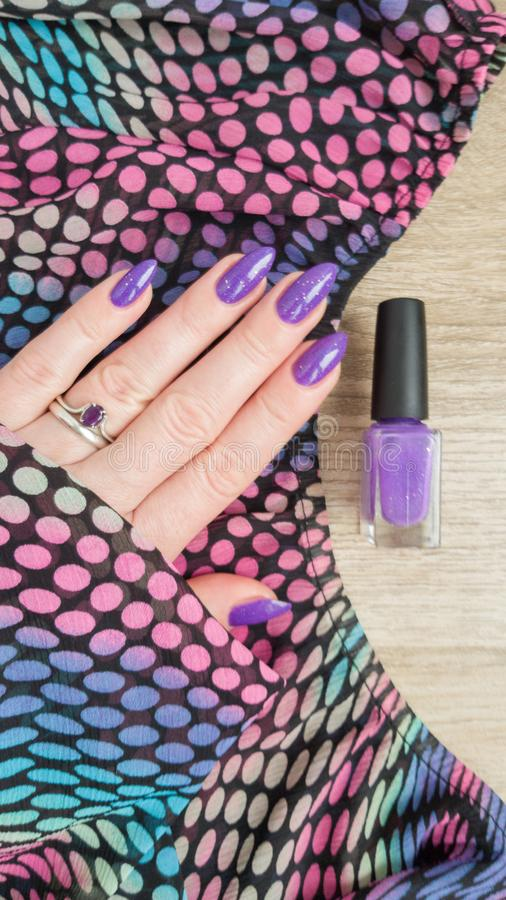 Female hand with purple violet long nails. And nail polish bottle stock images