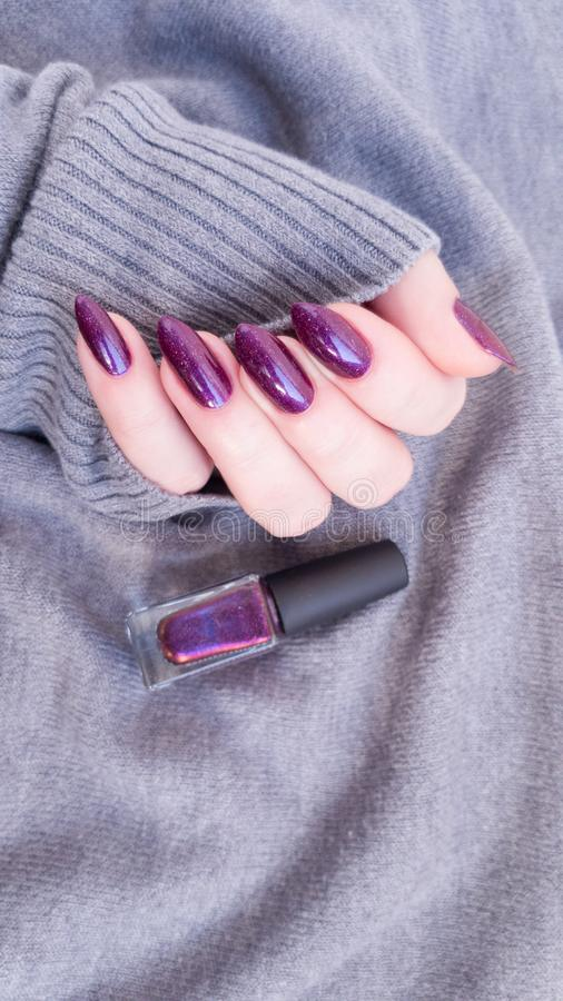 Female hand with purple violet long nails. And nail polish bottle stock photo