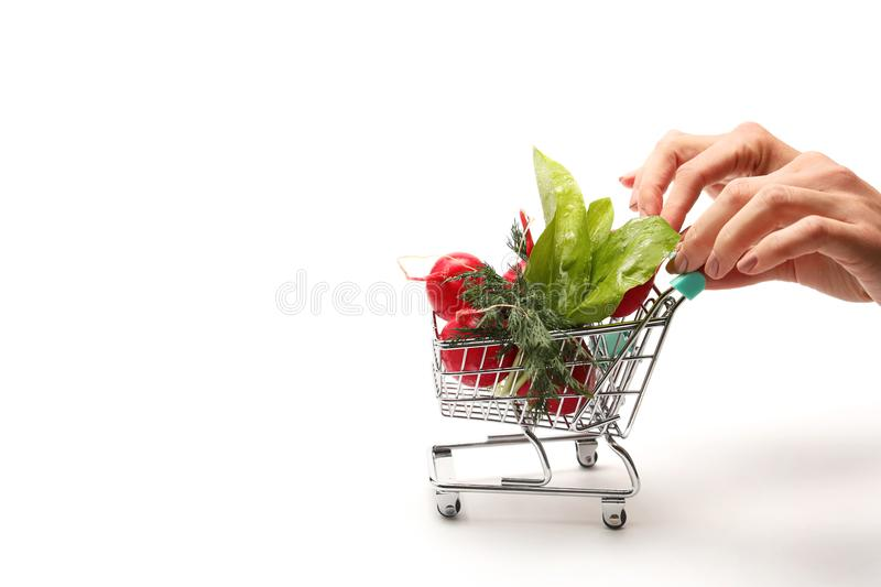 Hand pushing small shopping cart full with vegetables isolated on white background. Female hand pushing small shopping cart with radish and fresh leafs with stock photo