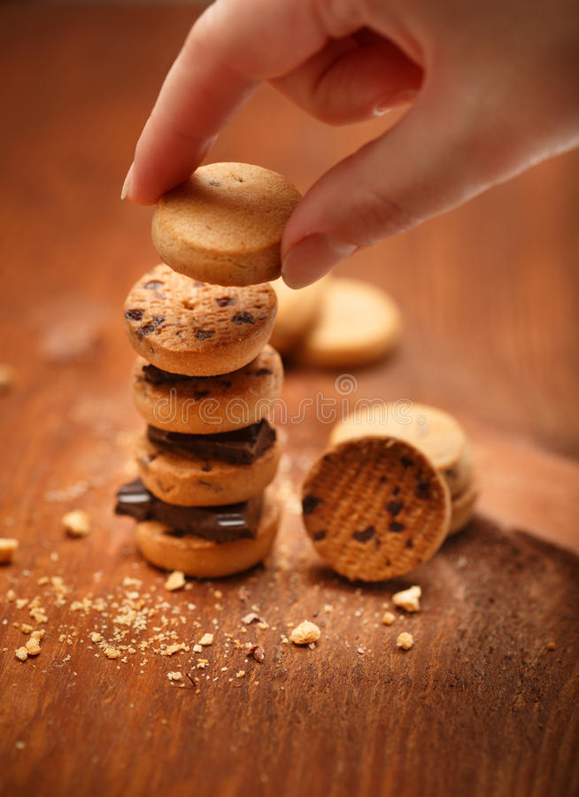 Female hand puts small bisqiut cookies on each other with chocolate pieces between and makes turret at wooden table background wi stock images