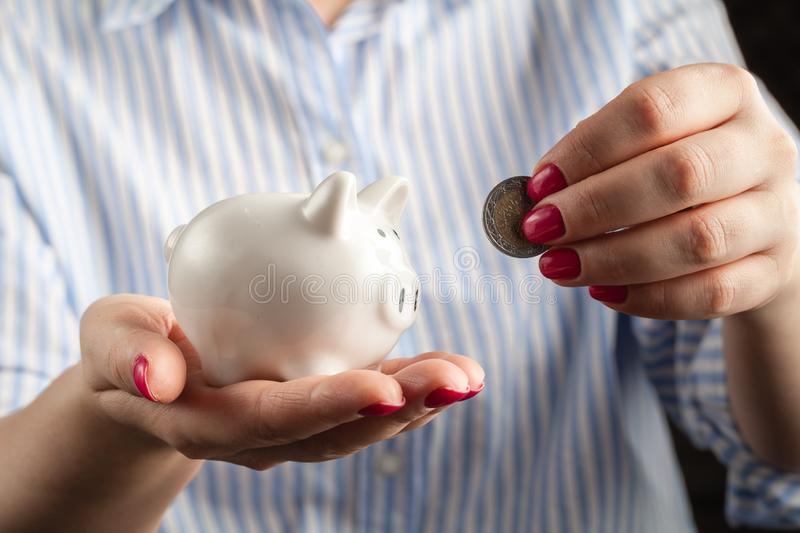 Female hand putting coin into piggy bank closeup royalty free stock image