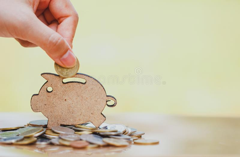 Female hand putting coin and stack of coins in concept of savings and money growing or energy save. Business investment growth concept,money saving. Investment stock image