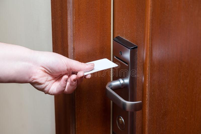 Female hand putting key card switch in to open hotel room door royalty free stock photography