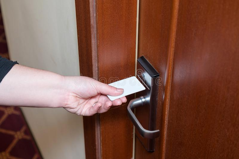 Female hand putting key card switch in to open hotel room door. Holding magnetic card for door access control scanning key card royalty free stock photo