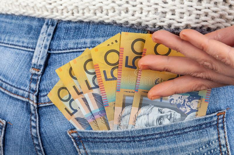 Female hand reaching for 50 Australian dollar bills. Female hand reaching for 50 Australian dollar bills in her jeans back pocket royalty free stock photo
