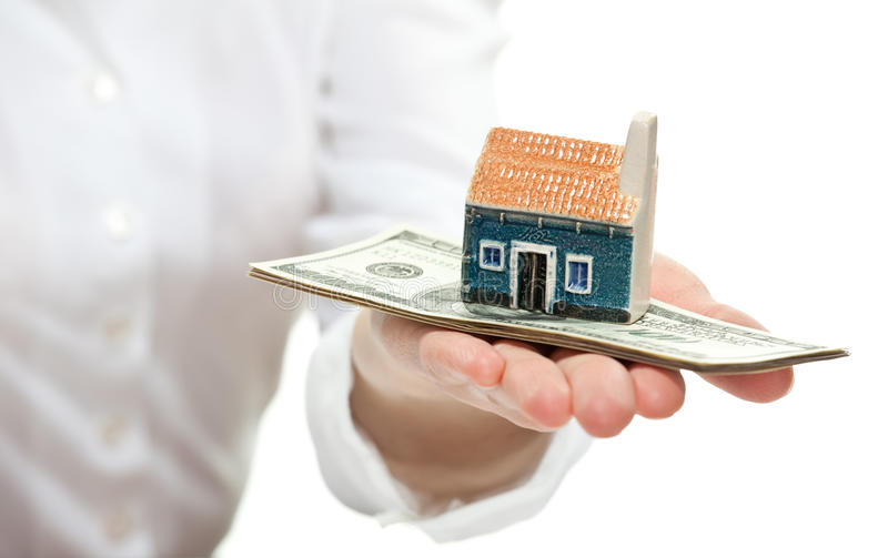 Female hand reaching out little house model to you. Concept of buying a house: female hand reaching out little house model to you royalty free stock photo