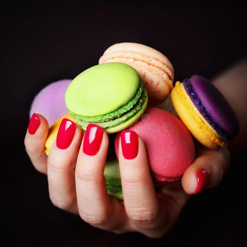 Female hand with red nails holding macarons royalty free stock photo