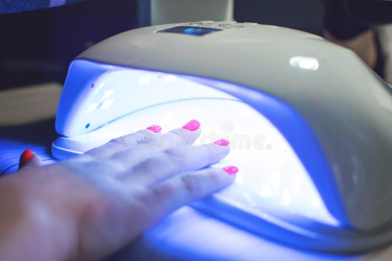 Female Hand with red nails in the lamp for manicure. Nail Lamp Dryer for Gel Nail Polish Curing Manicure Pedicure royalty free stock photos
