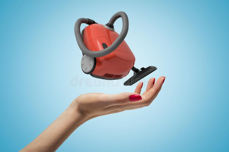 Female hand with red vacuum cleaner on blue background stock photo