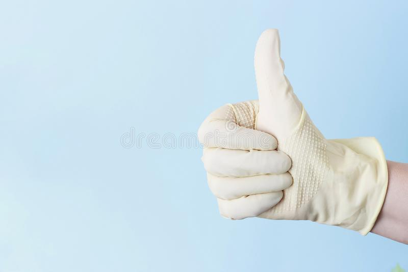 Female hand in rubber white gloves with raised up his thumb on a blue background stock photo
