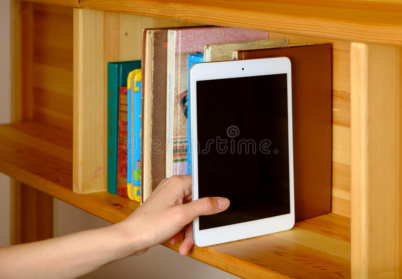 Female hand selecting book from a bookshelf royalty free stock photos