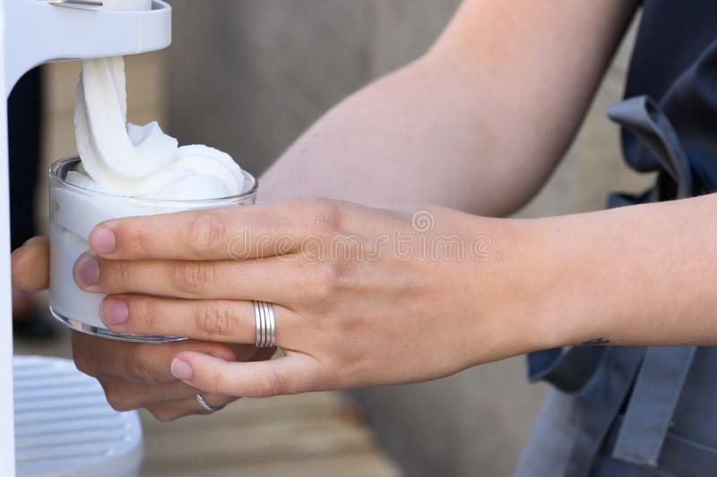 Female hand serving soft ice cream from a machine royalty free stock photography
