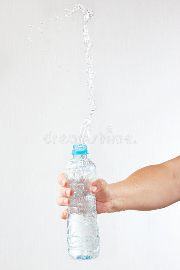 Female hand shaking a bottle of fresh water with splash. Female hand shaking a bottle of fresh water with a splash royalty free stock photography