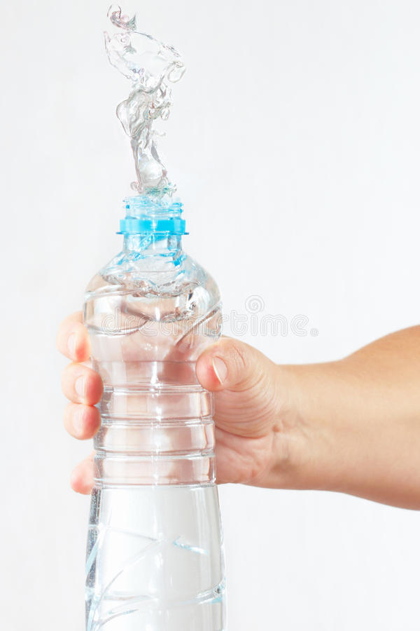 Female hand shaking bottle of water with a splash. Female hand shaking a bottle of water with a splash royalty free stock photo