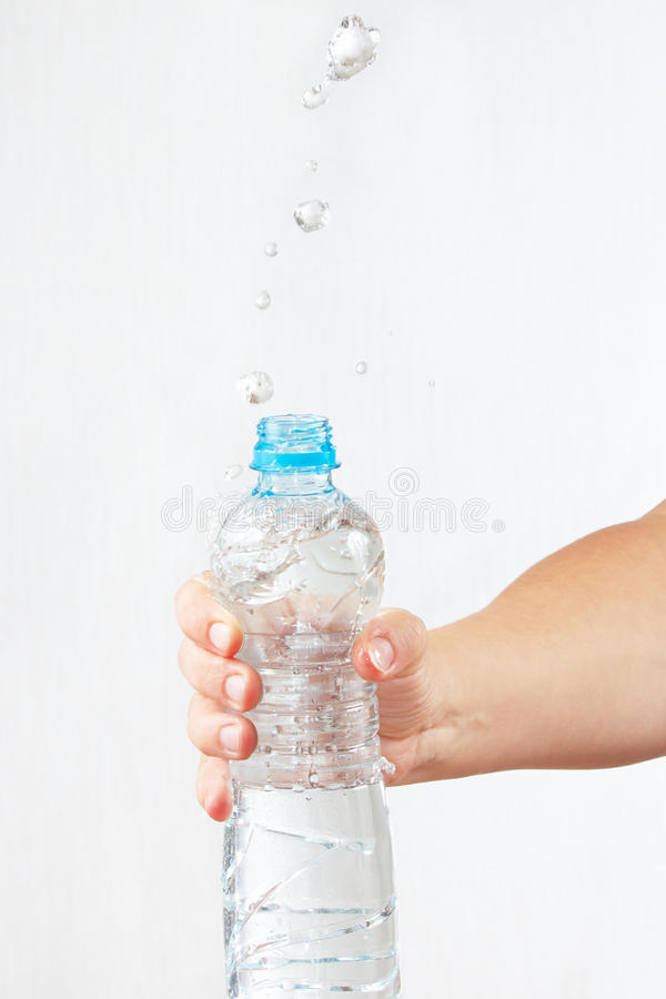 Female hand shaking a small bottle of mineral water with splash. Female hand shaking a small bottle of mineral water with a splash royalty free stock image