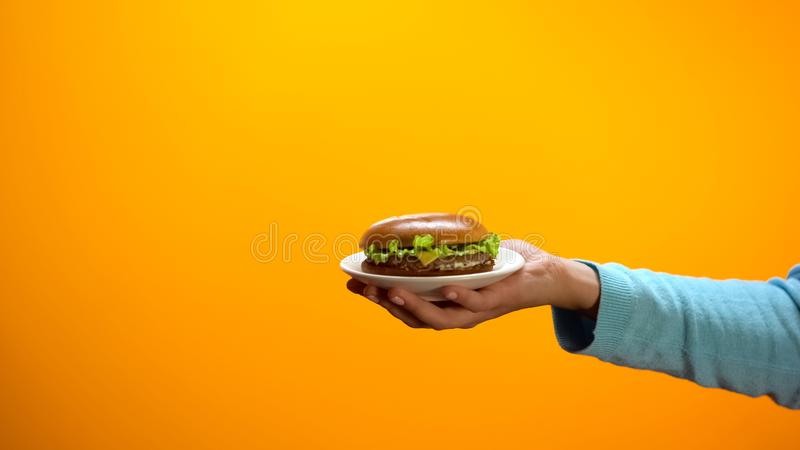 Female hand showing cheeseburger, inviting customers to fast food restaurant royalty free stock photo