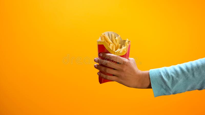 Female hand showing french fries, inviting customers to fast food restaurant stock photo