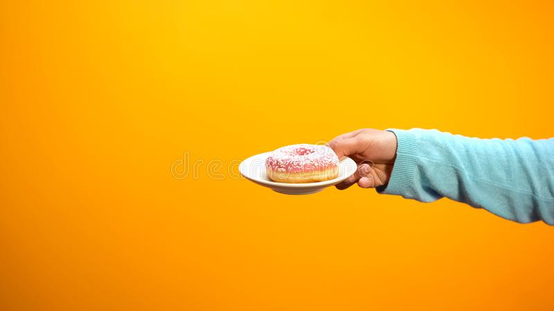 Female hand showing sweet donut, inviting customers to confectionary store stock photography