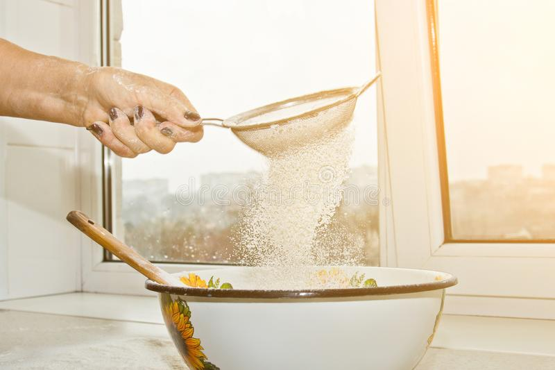 Female hand sifting flour through manual flour sieve in a bowl close-up copy space. cooking dough. metal kitchen appliance stock image