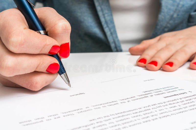 Female hand signing contract to conclude a deal stock image