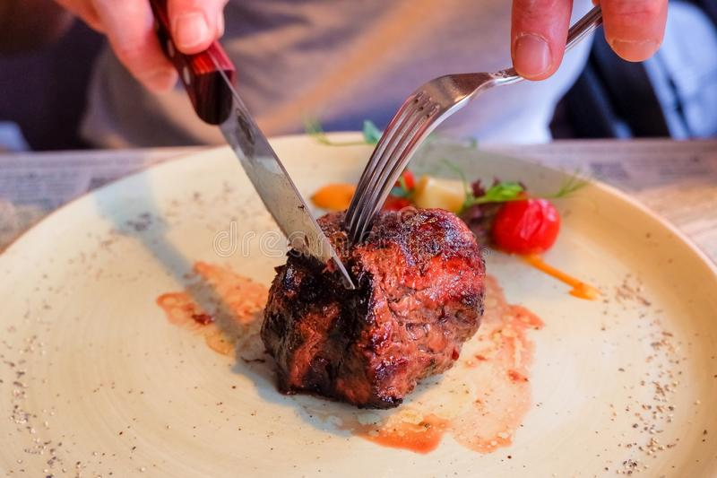 Hands are slicing steak in the restaurant.eating stake from plate with fork and knife man hands.cutting grilled beef stock image