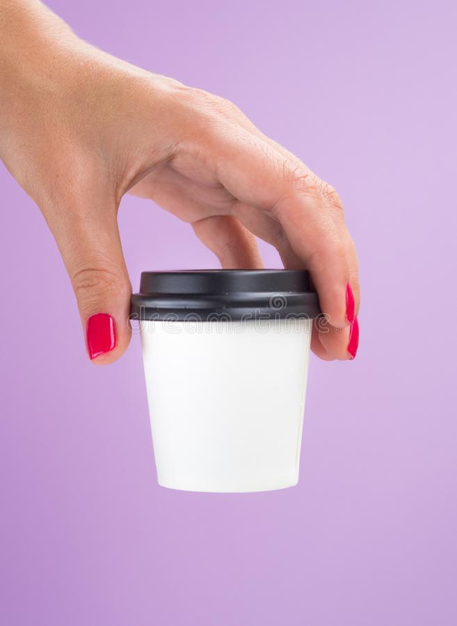 Female hand with small paper coffee cup isolated on a pink background. White espresso cup mockup with copy space.  stock image