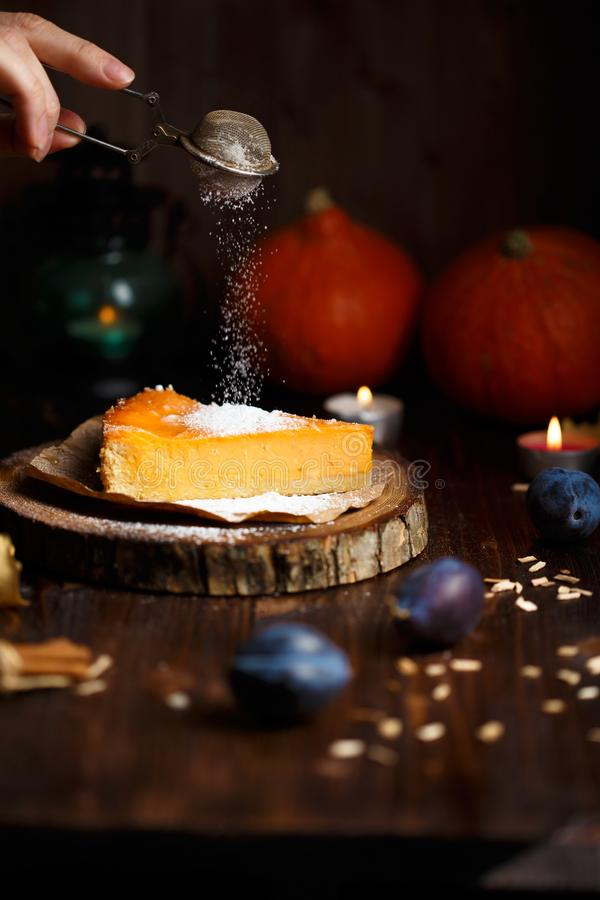 Female hand sprinkles powdered sugar on pumpkin cheesecake. Pumpkins, table lamp, foliage, vanilla on a wooden dark background. stock image