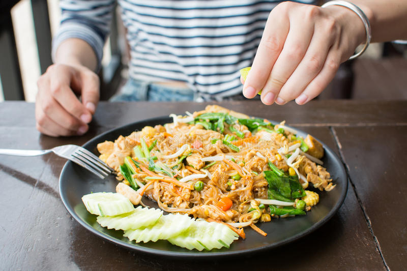 Female hand squeezing lime on Pad Thai royalty free stock photos