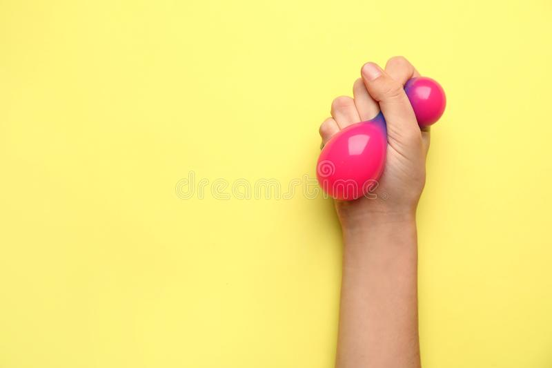Female hand squeezing stress ball on color background stock photos