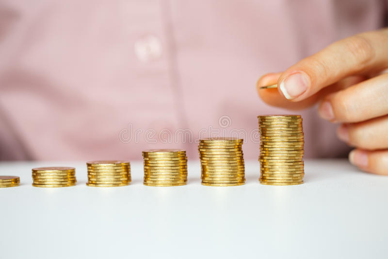 Female hand stacking gold coins into increasing columns. Savings, female hand stacking gold coins into increasing columns royalty free stock photography