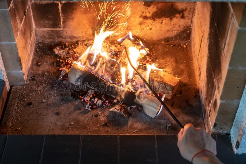Female hand straightens and overturns burning firewood with an iron poker in an open fireplace and from the coal fly royalty free stock photo