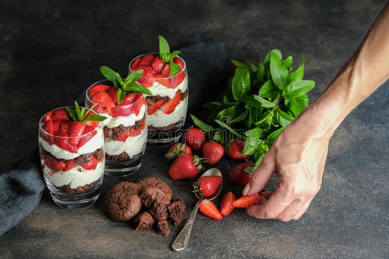 Female hand and strawberry dessert. Trifles with fresh strawberries, mint, chocolate biscuit and delicate cream. royalty free stock photo