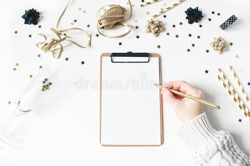 Female hand in sweater and writing. New year resolution, wish list concept. Blank notebook mockup. Golden party. Decoration, confetti and wine glass on white stock images