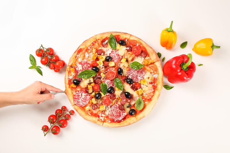 Female hand take pizza piece. Flat lay composition royalty free stock image