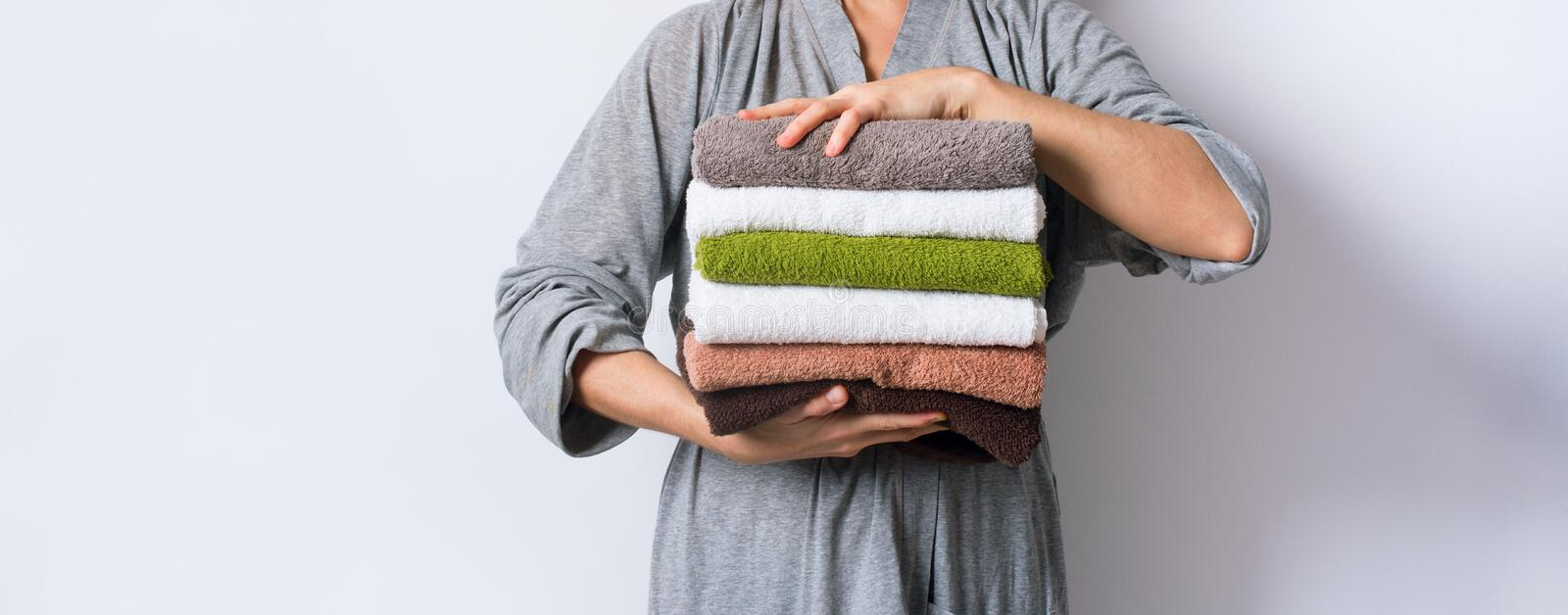 Female hand take stack bath towels colorful cotton. Female hand holding stack clean bath towels colorful cotton terry textile background closeup royalty free stock photos