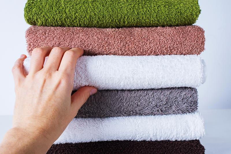 Female hand take stack bath towels colorful cotton. Terry textile background closeup royalty free stock photos