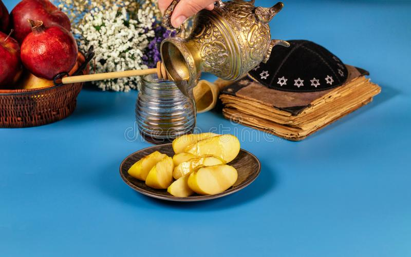 A female hand takes a with honey for the apple slice and pomegranate holiday of Rosh Ha Shana. Jewish prays at the praying book, holidays, new, year, hashana stock photos