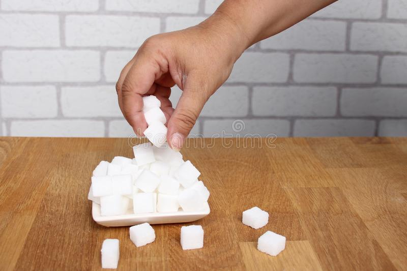 Female hand takes refined sugar from a sugar bowl in pieces on a wooden table, concept of excess sugar intake, diabetic, closeup,. Copy space stock photography